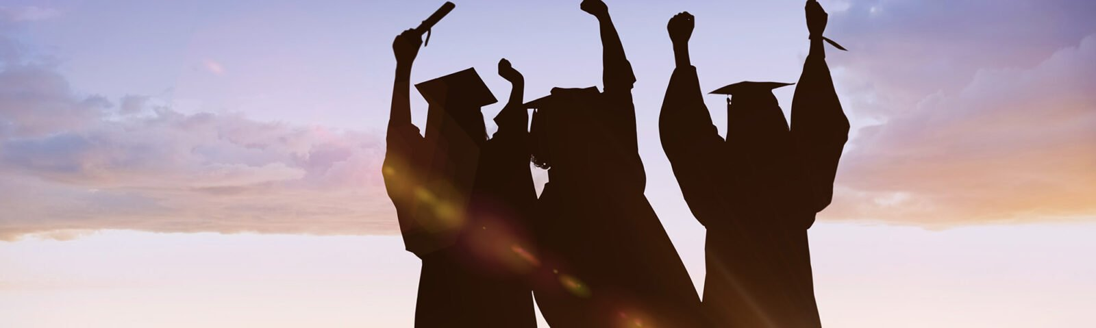 group of graduates in silhouettes with their grad caps on and their hands and diplomas raised