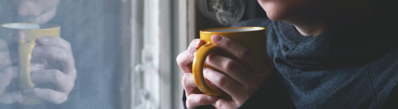 Young hands holding a steaming yellow cup while in a blue sweater